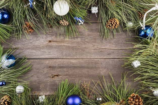Fir withtree and christmas jewelry on a wooden frame background