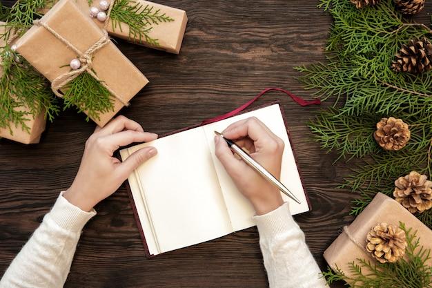 女性の手がギフトとfirコーンと暗いボード上のノートにクリスマスの手紙を書く