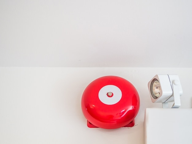 Fire alarm bell and emergency lighting on grey wall
