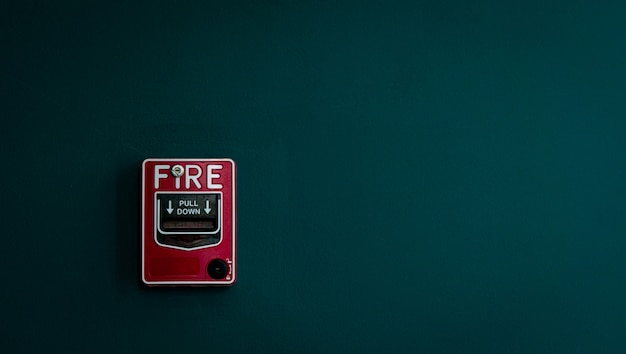 Fire alarm on dark green concrete wall
