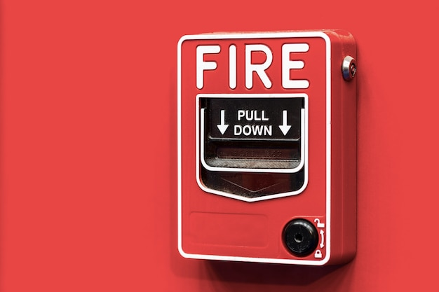 Fire alarm switch on red wall.