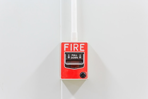 Fire alarm switch on white factory wall for warning and security system