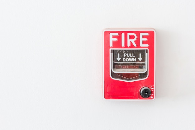 Fire alarm switch on white wall as background for warning and security system.