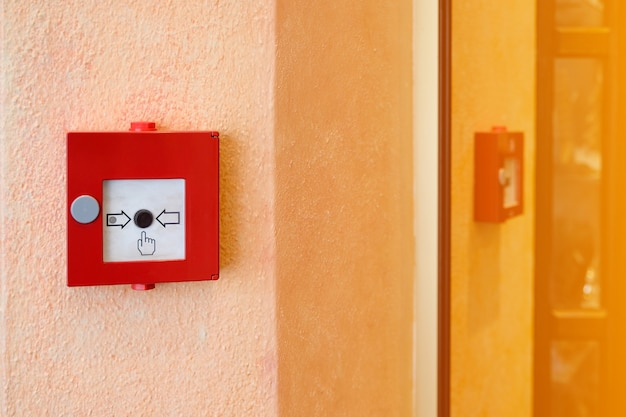 Fire alarm system in red box installed on wall of building.