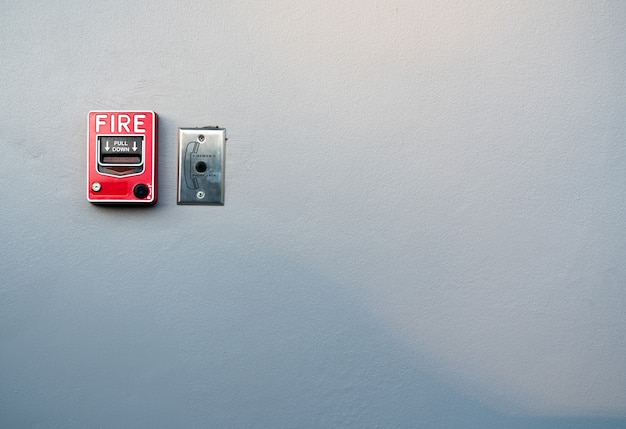 Fire alarm on white concrete wall. warning and security system. emergency equipment for safety alert. red box of fire alarm.