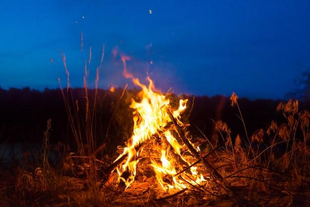 별이 있는 밤하늘 아래 산에서 밤에 불