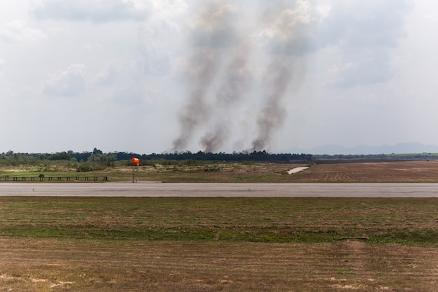 Fire burns near the airport with smoke from fire cause bad pollution.