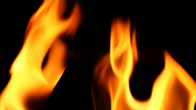 火のクローズアップと赤オレンジ黄色の詳細テクスチャと黒の背景の抽象的な形。