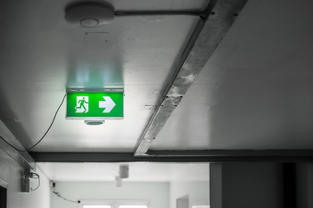 Fire emergency exit sign on the wall background inside building. safety concept