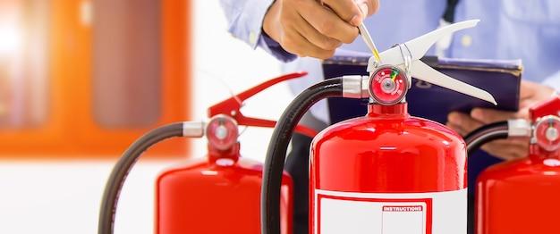 Пожарная техника проверяет манометр уровня огнетушителя.