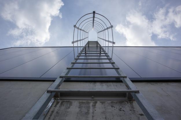Пожарная лестница на промышленном здании наверху, вид снизу. поручни из нержавеющей стали, лестница на крышу. детальный вид лестницы с каркасом безопасности. концепция строительства здания.