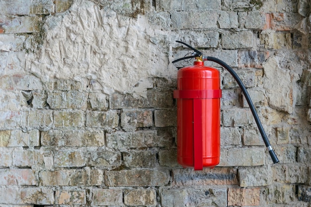Fire extinguisher on a brick wall construction building location