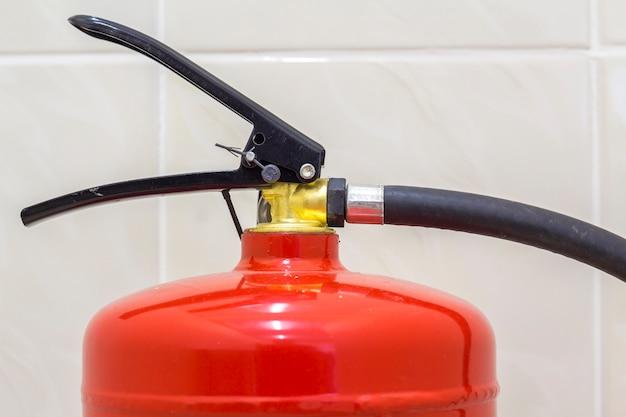 白色光のタイル壁と床コピースペース背景に分離された消火器明るい赤。危険と安全性、防火コンセプト。