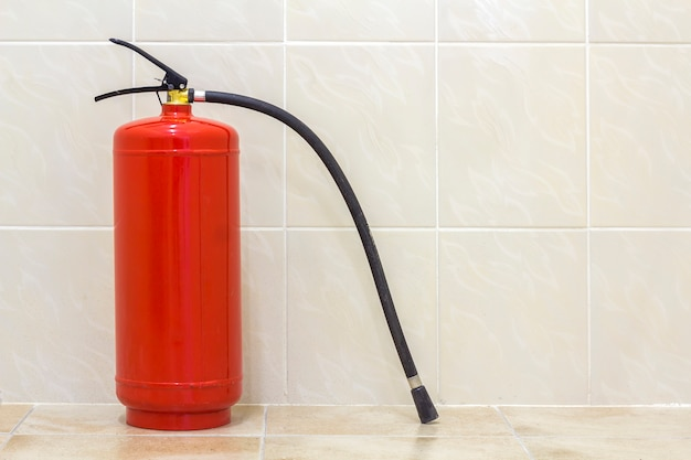 Fire extinguisher bright red isolated on white light tiles walls and floor