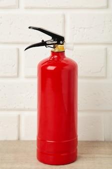 Огнетушитель на белой кирпичной стене с обтравочным контуром