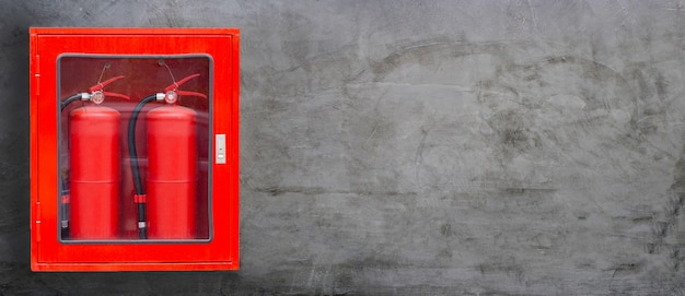 Fire extinguisher in red cabinet on concrete wall background.