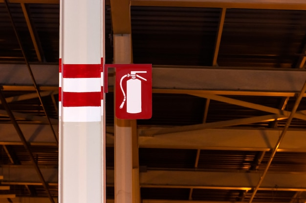 Знак огнетушителя прикреплен к столбу на стальной балке в промышленности