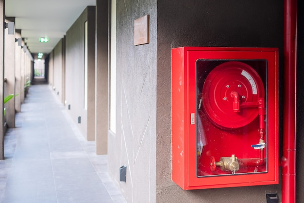 Fire extinguisher and water pump system on the wall background, powerful emergency equipment for industrial and residential
