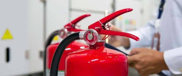 消防士が建物内の赤い消火器タンクの圧力計をチェックしています