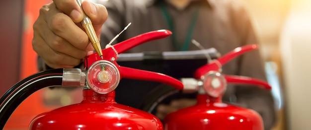 消防士は赤い消火器タンクの圧力計をチェックしています