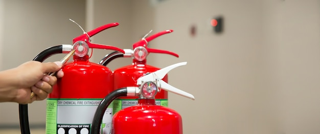 消防士は建物の赤い消火器タンクをチェックしています。