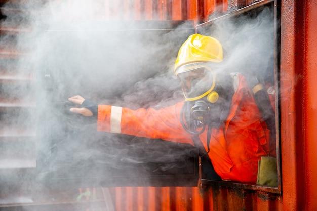Пожарный в форме оранжевого цвета открывает окно для выпуска дыма в случае крайней необходимости. открытое окно для спасения человека.
