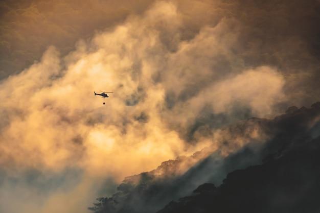 Пожарный вертолет несет ведро с водой для тушения лесного пожара