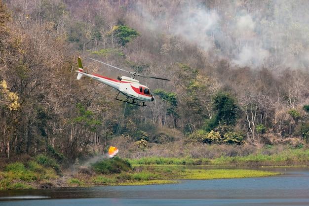 Пожарный вертолет несет воду для тушения лесного пожара