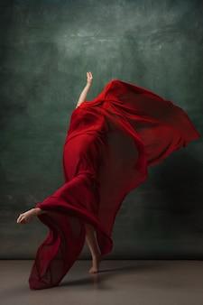 火炎。暗いスタジオの背景で踊る優雅な古典的なバレリーナ。真っ赤な布。優雅さ、芸術家、動き、行動、動きの概念。無重力で柔軟に見えます。ファッションスタイル。