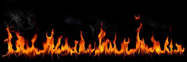 黒の背景に煙と火の炎燃える赤い熱い火花が上がる