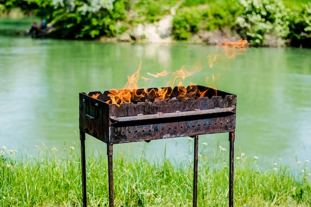 Fire in the grill on the river bank