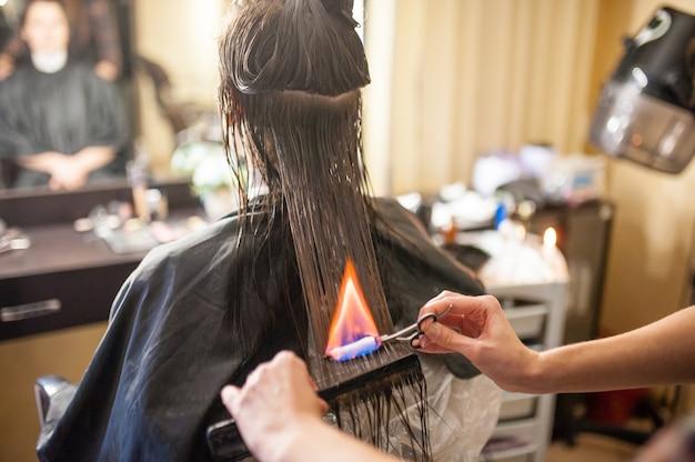 Обработка волос огнем в салоне красоты.