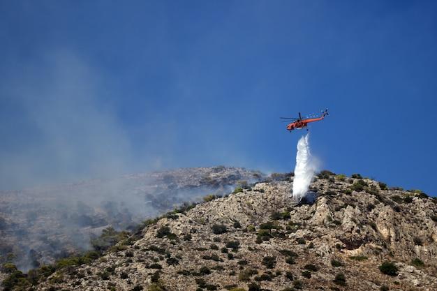 소방 헬리콥터가 언덕에서 화재를 진압합니다. 그리스. 여름이 끝났습니다.