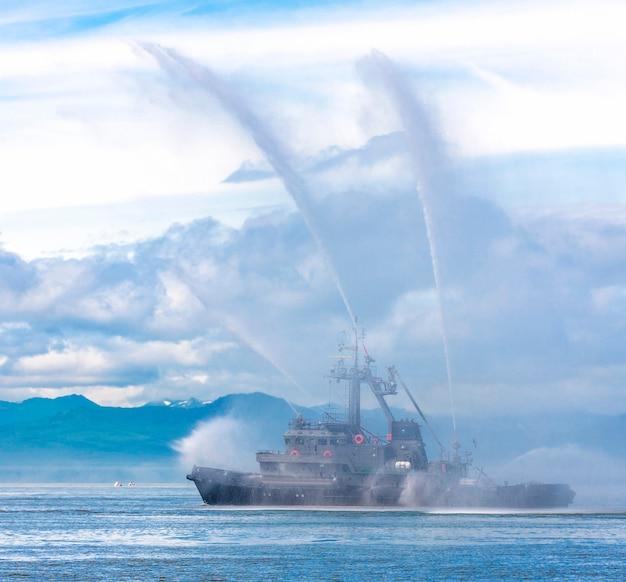 태평양의 캄차카에 물을 뿌리는 소방 호스 보트