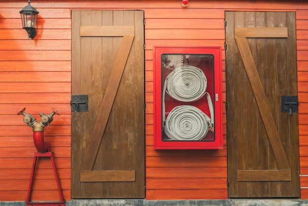 Fire hose in red cabinet hanging on orange wooden wall.