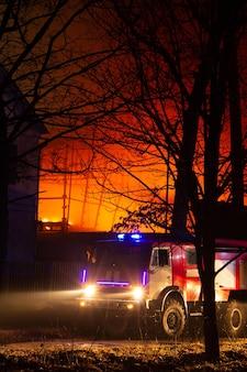 夜に工場の建物で火災。消防士は火を消そうとします