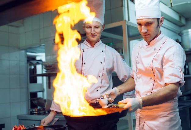 Огонь на кухне. огонь газовый ожог готовит на сковороде, очень горячий огонь