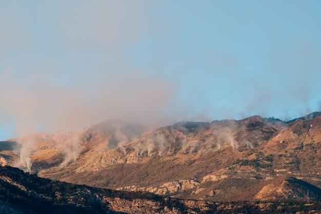 Пожар в горах днем дым над горами