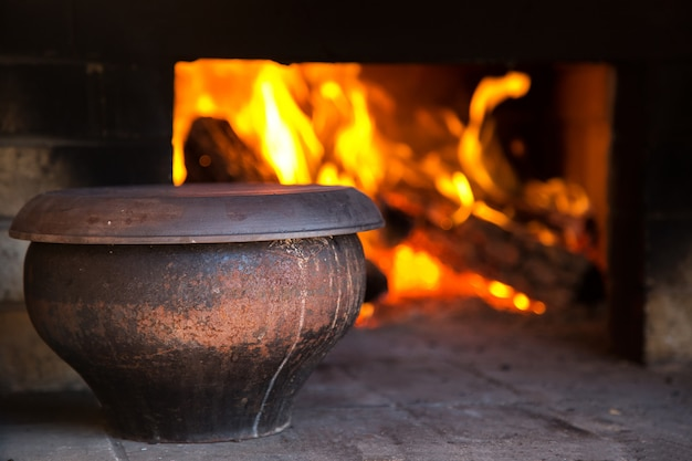 The fire in the old traditional russian village oven in a rustic style.  pot of soup near the burning wood