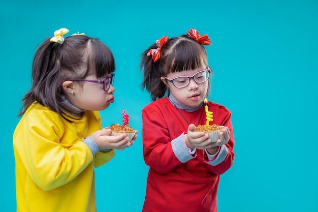 Огонь на свече. любопытные сестры-близнецы с психическим расстройством внимательно рассматривают праздничные торты