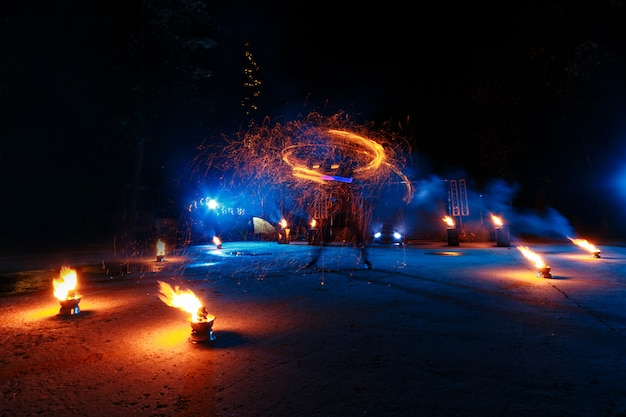 Fire show, dancing with flame, draws a fiery figure in the dark, bright sparks in the night.
