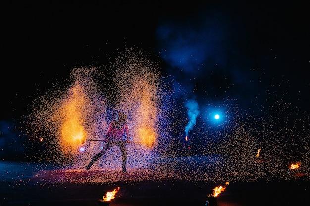 火のショー、炎で踊る、花火でジャグリングする男性のマスター、屋外でのパフォーマンスは、夜の暗くて明るい火花の中で燃えるような姿を描きます。 ledのスーツを着た男が火で踊る。
