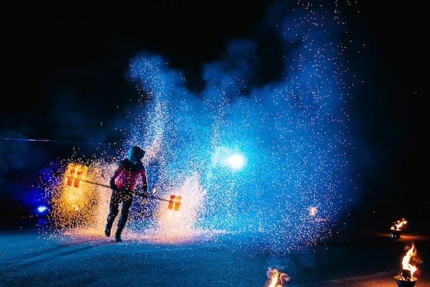 Огненное шоу, танцы с пламенем, мастер-мужчина, жонглирующий фейерверком, выступление на открытом воздухе, рисует огненную фигуру в темноте, яркие искры в ночи. мужчина в светодиодном костюме танцует с огнем.