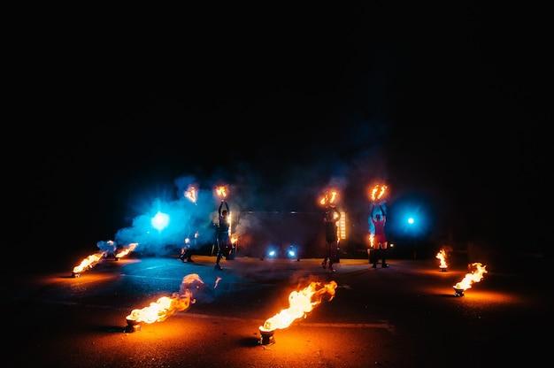 火のショー、炎で踊る、花火でジャグリングする男性のマスター、屋外でのパフォーマンス、人々は夜の暗くて明るい火花の中で燃えるような姿を描きます。 ledのスーツを着た男が火で踊る。