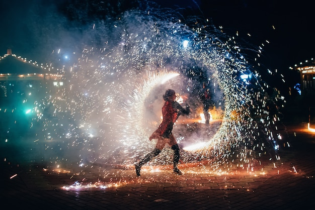 Fire show. girl spins fiery sparkling torches