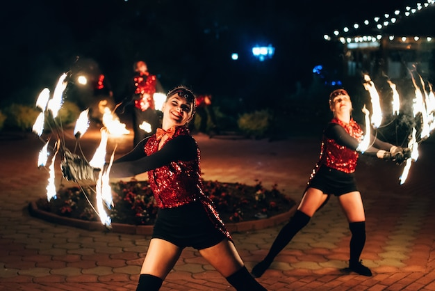 Fire show. girls dancers spin torches of fire.