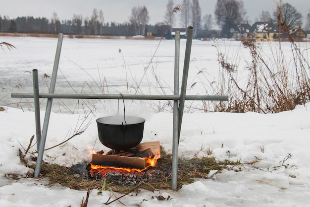 Above a fire there is a pot, meal, in winter in a hike at the small river