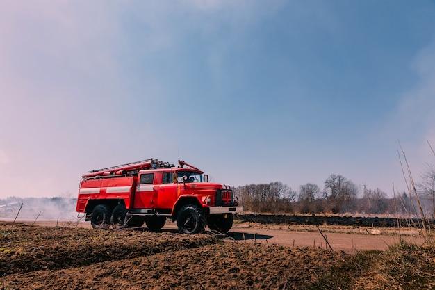 Пожарная машина на горящем поле с дымом