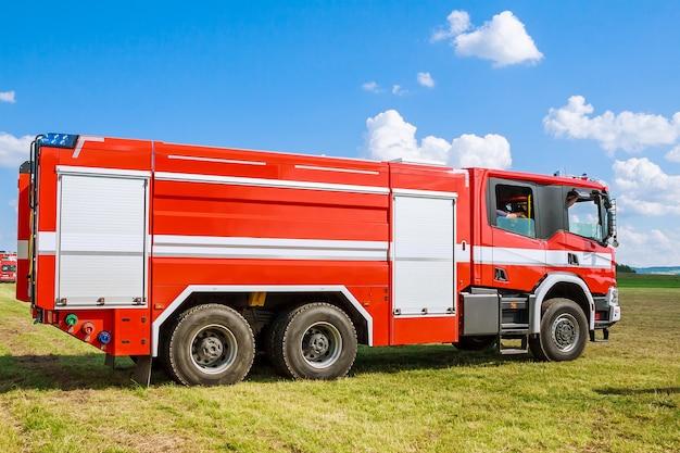青い空の下のフィールドで消防車。救助者。