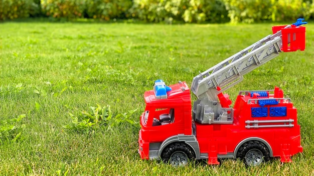 Fire truck toy on green grass. toys. copy space